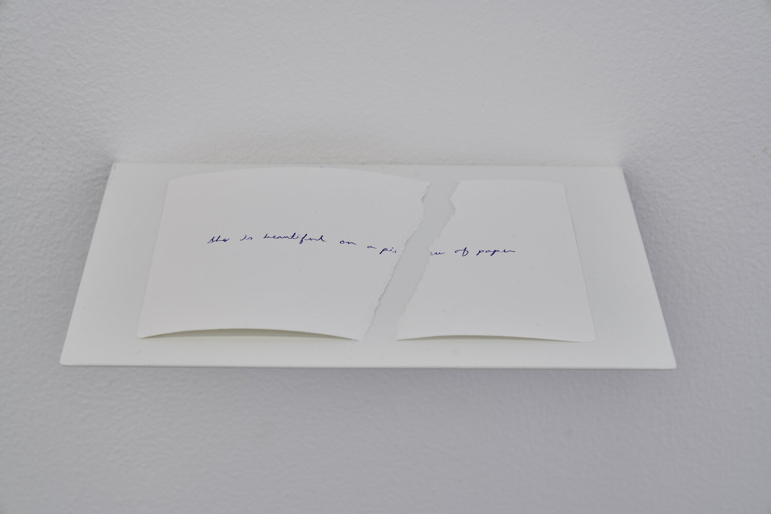 She is beautiful on a piece of paper 2019 Handwritten text on paper, metal shelf Dimensions variable