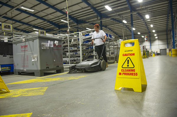 Warehouse cleaning with safety signage displayed