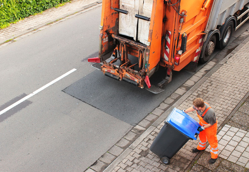 Man emptying waste bin into lorry for office waste collection