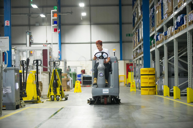 Using warehouse floor cleaning machine