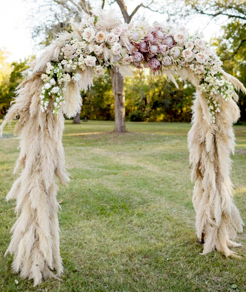 Intricate floral archway designed for an outdoor wedding alter by Bouquets & Beyond