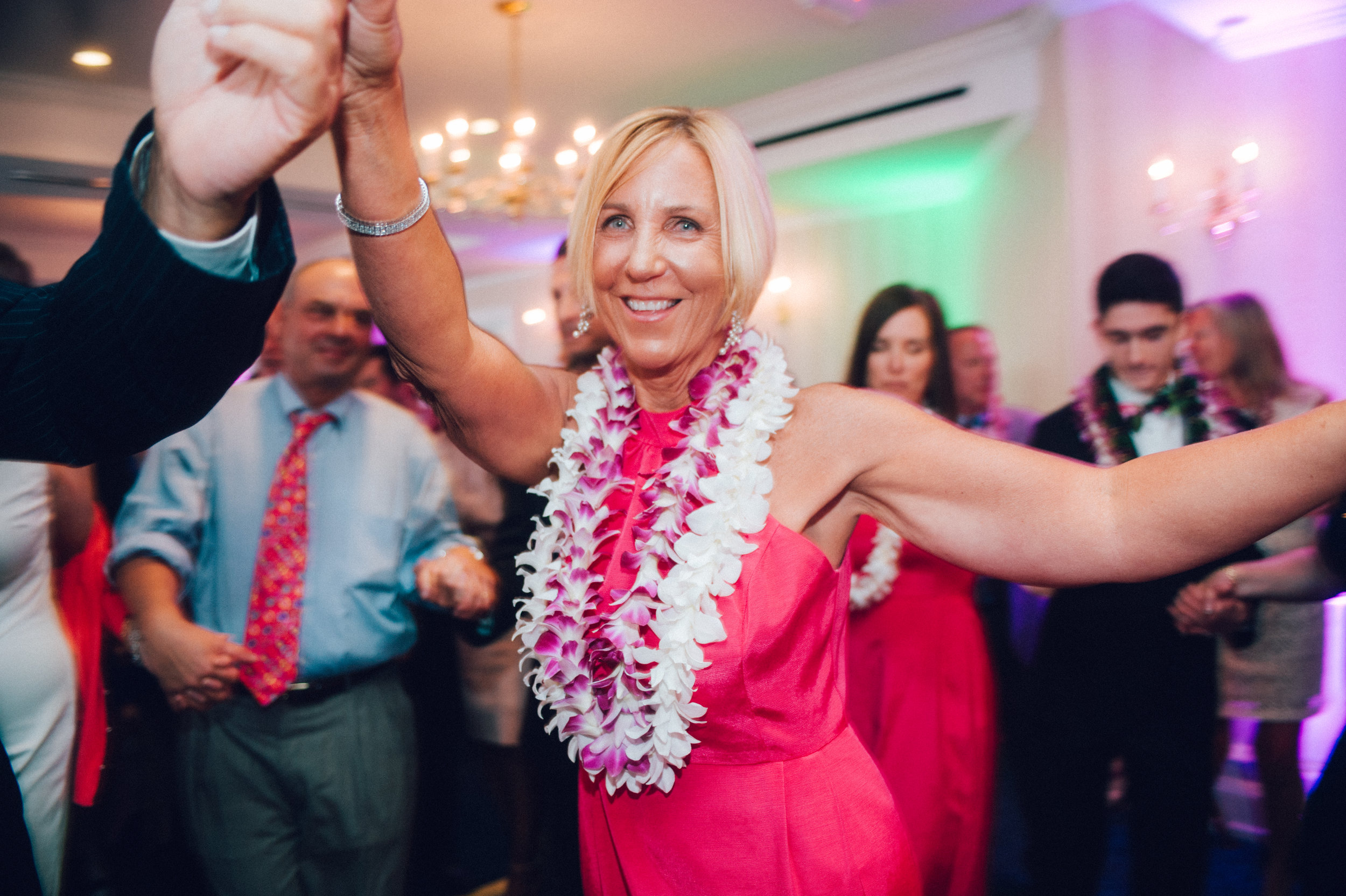 Mother of the bride dances at the wedding with orchid leis around her neck