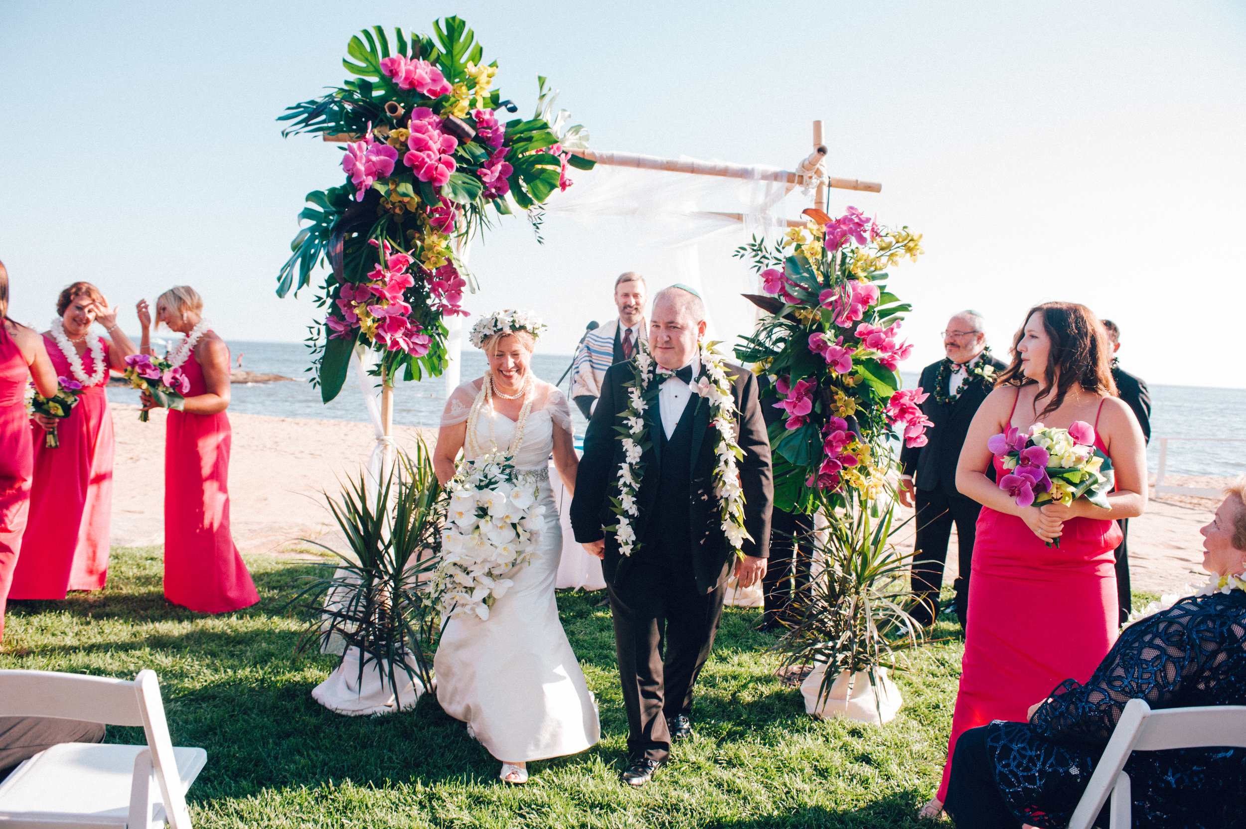 Bride and Groom getting married outdoors with beauitful floral arrangements surrounding them
