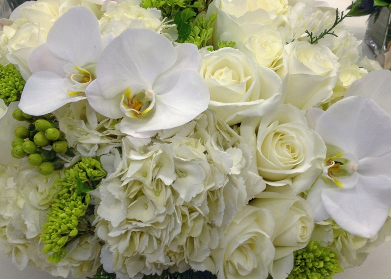 White orchids and roses among other flowers from Bouquets & Beyond