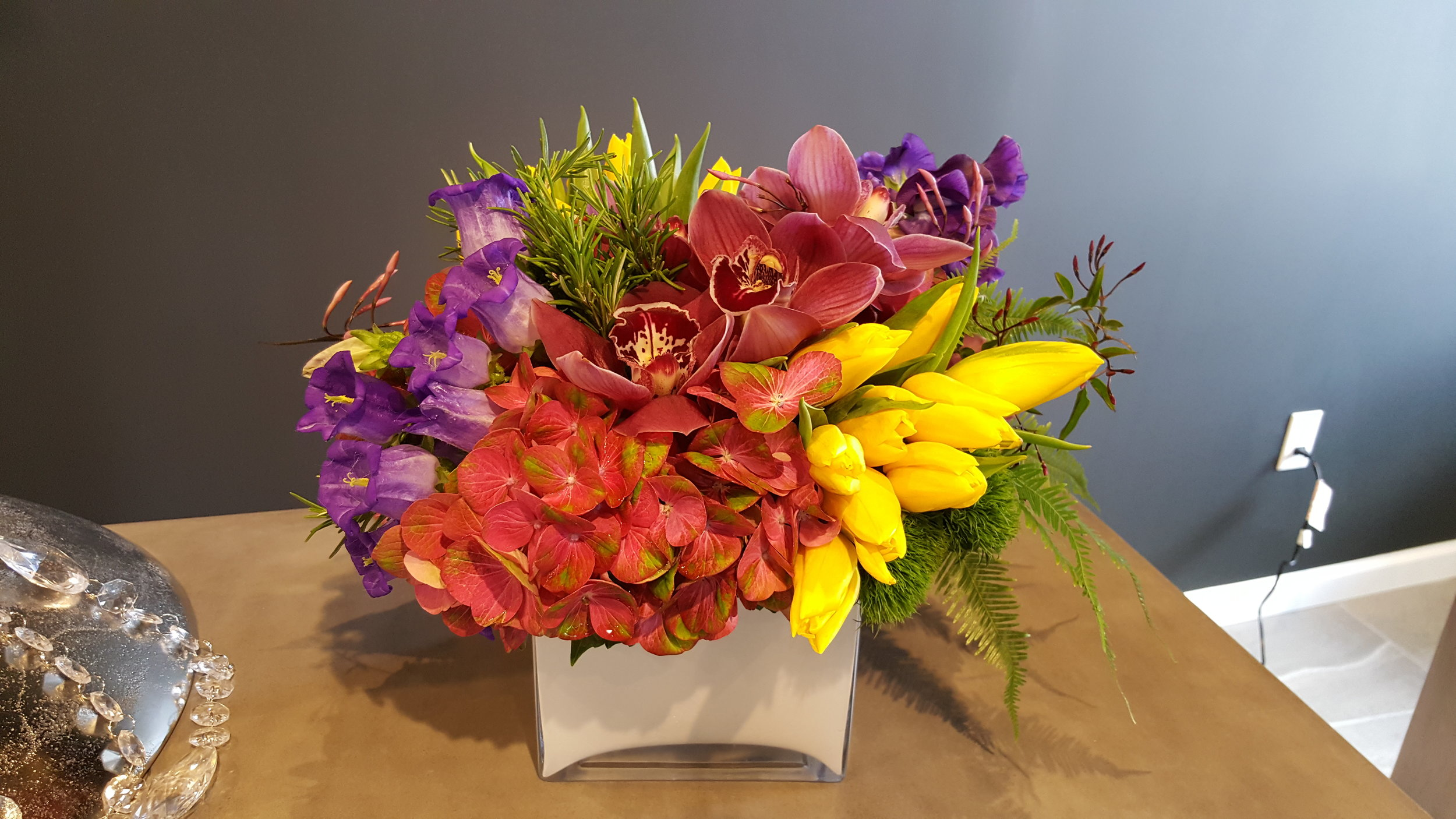Vibrant and bright floral arrangement designed by Bouquets & Beyond of Woodbury