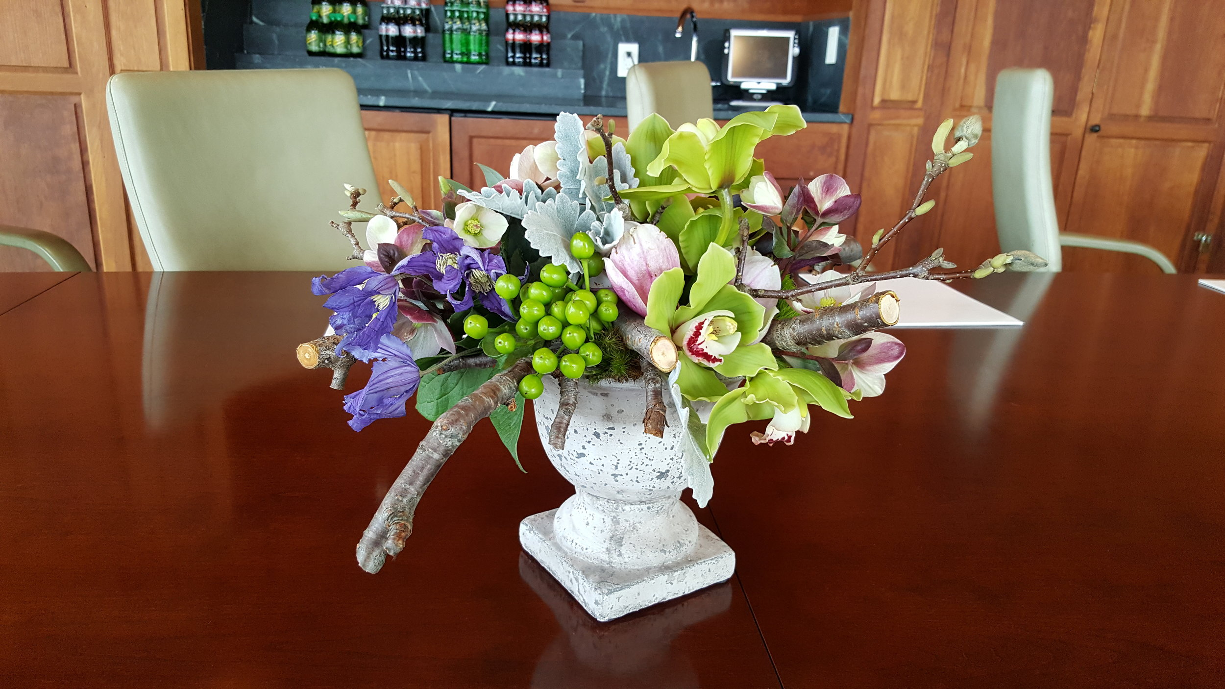 Conference table centerpiece of sticks, fruit and florals in a stone urn designed by Bouquets & Beyond