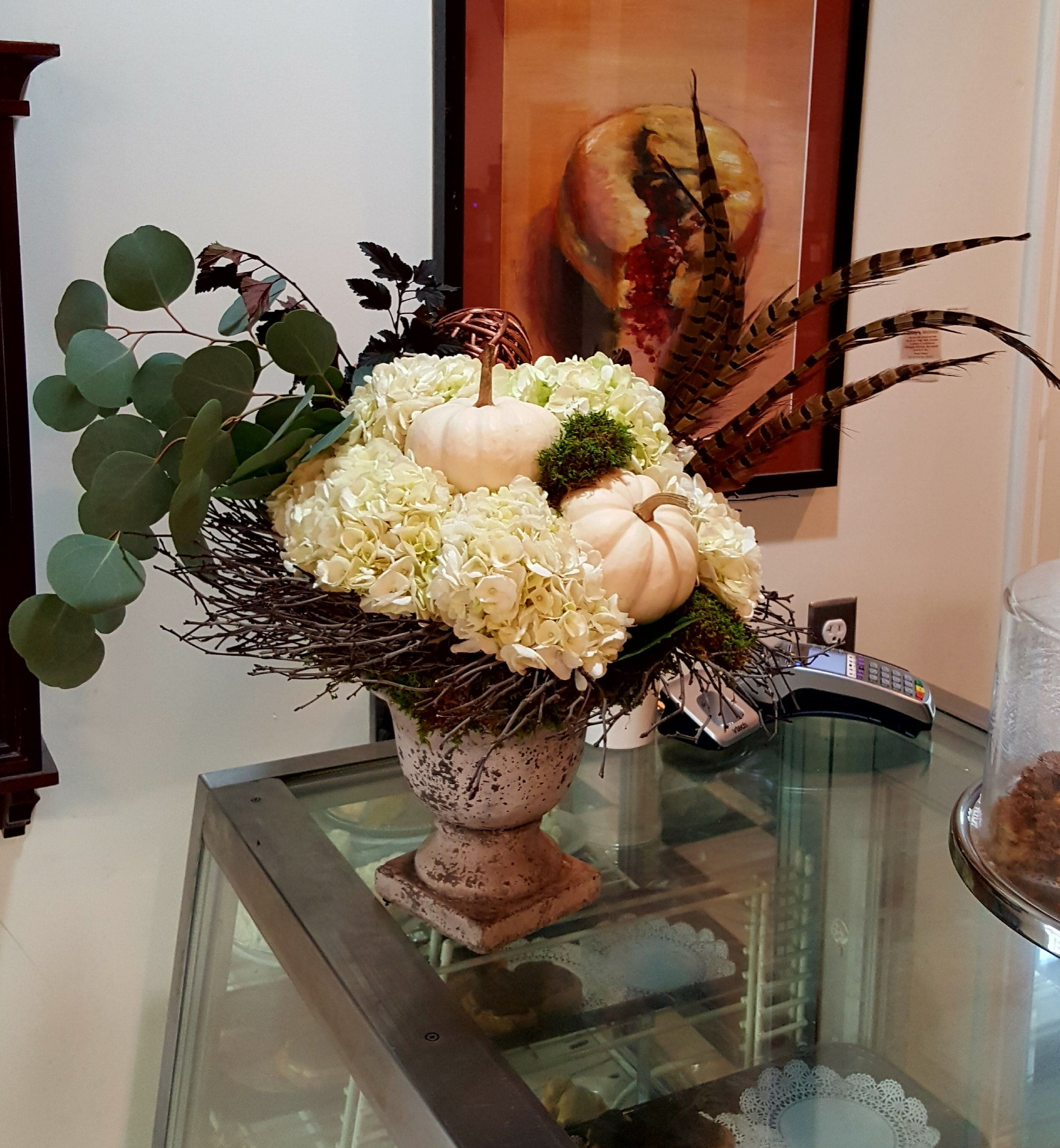 Hydrangeas, white gourds and feathers arrangement for office decor