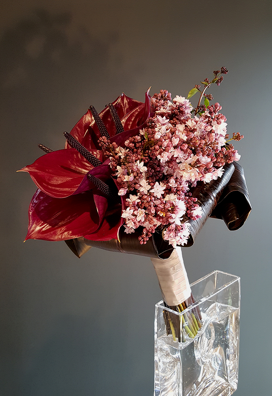 Bouquet of red flowers in an elegant glass vase designed by Bouquets & Beyond