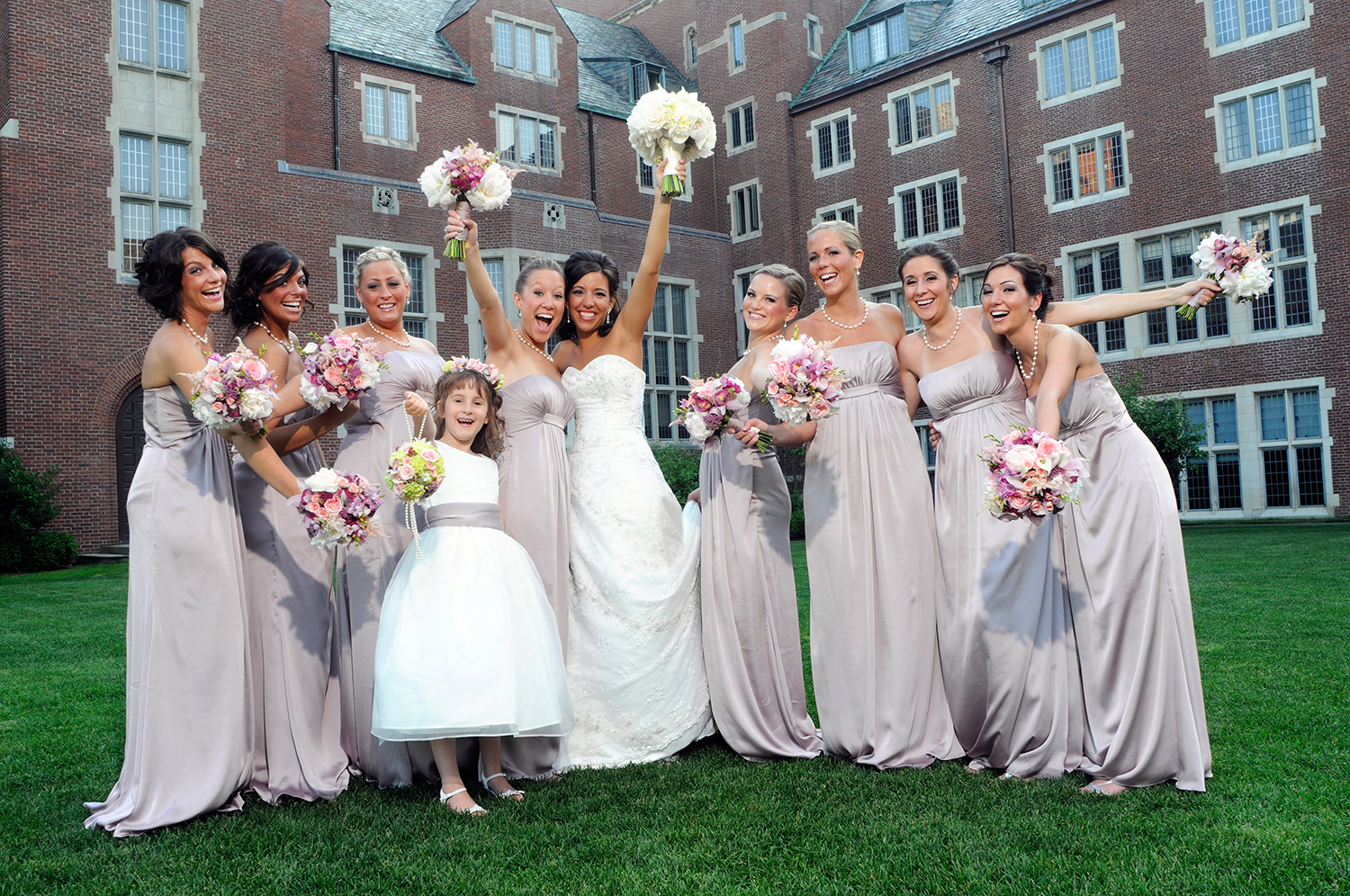 Wedding party poses for picture outside holding their bouquets in the air