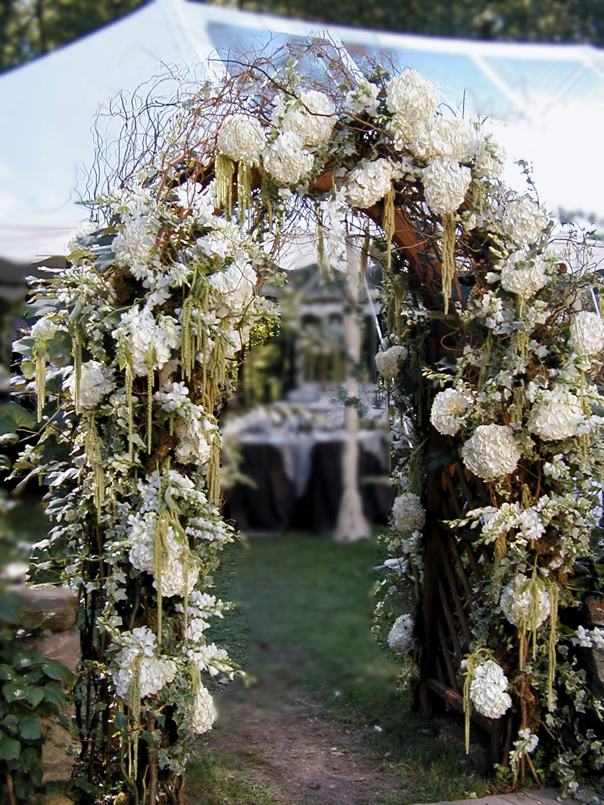 Woodsy floral wedding arch designed by Bouquets & Beyond
