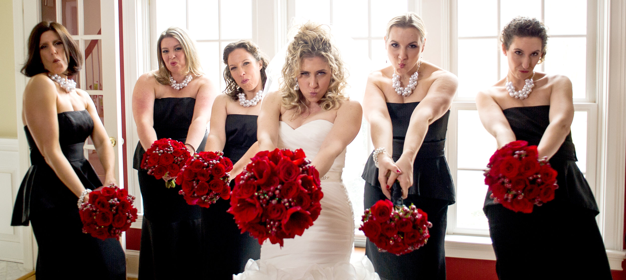Bride in white and bridesmaids in black dresses hold their bold red rose bouquets