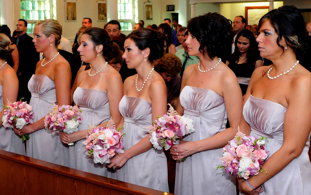 Bridesmaids with pink bouquets stand in a church during a wedding