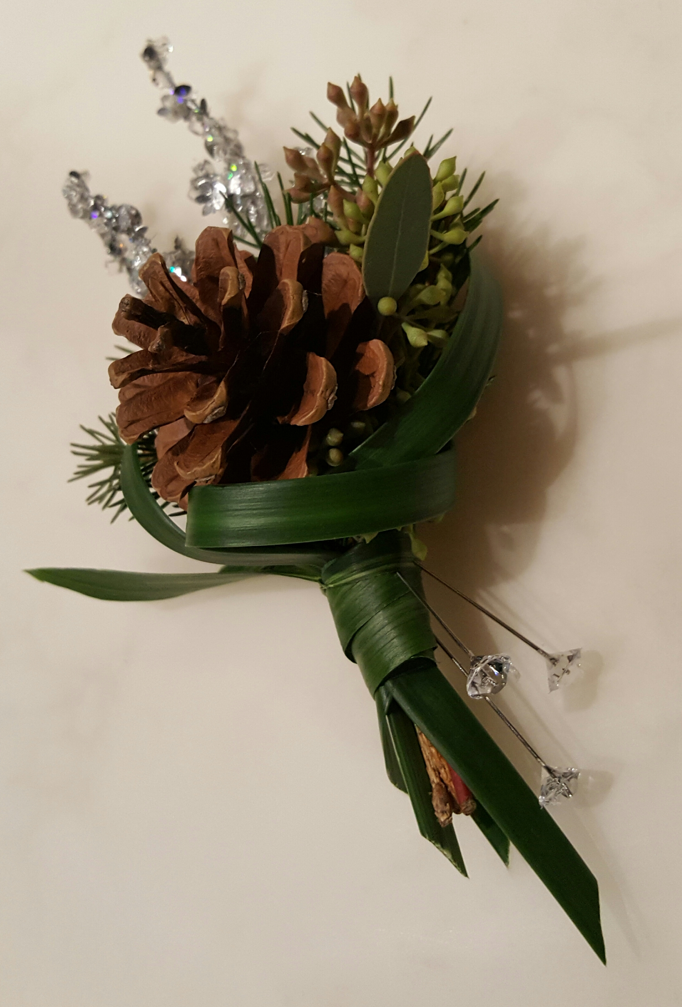 Pine cone in a floral arrangement designed by Bouquets & Beyond