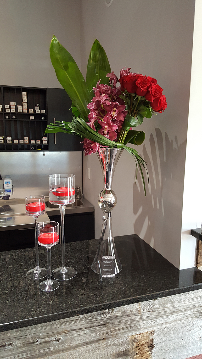 Red flowers in simple vase with decorative candles for restaurant decor