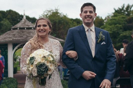 Bride and Groom smiling with flowers from Bouquets & Beyond