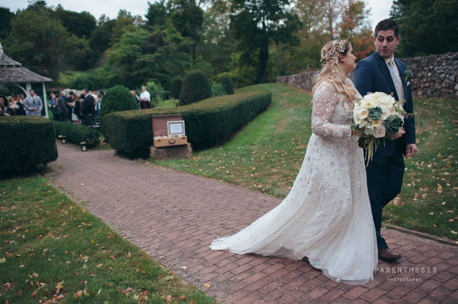 Bride walks with groom holding a luxurious bouquet of white flowers