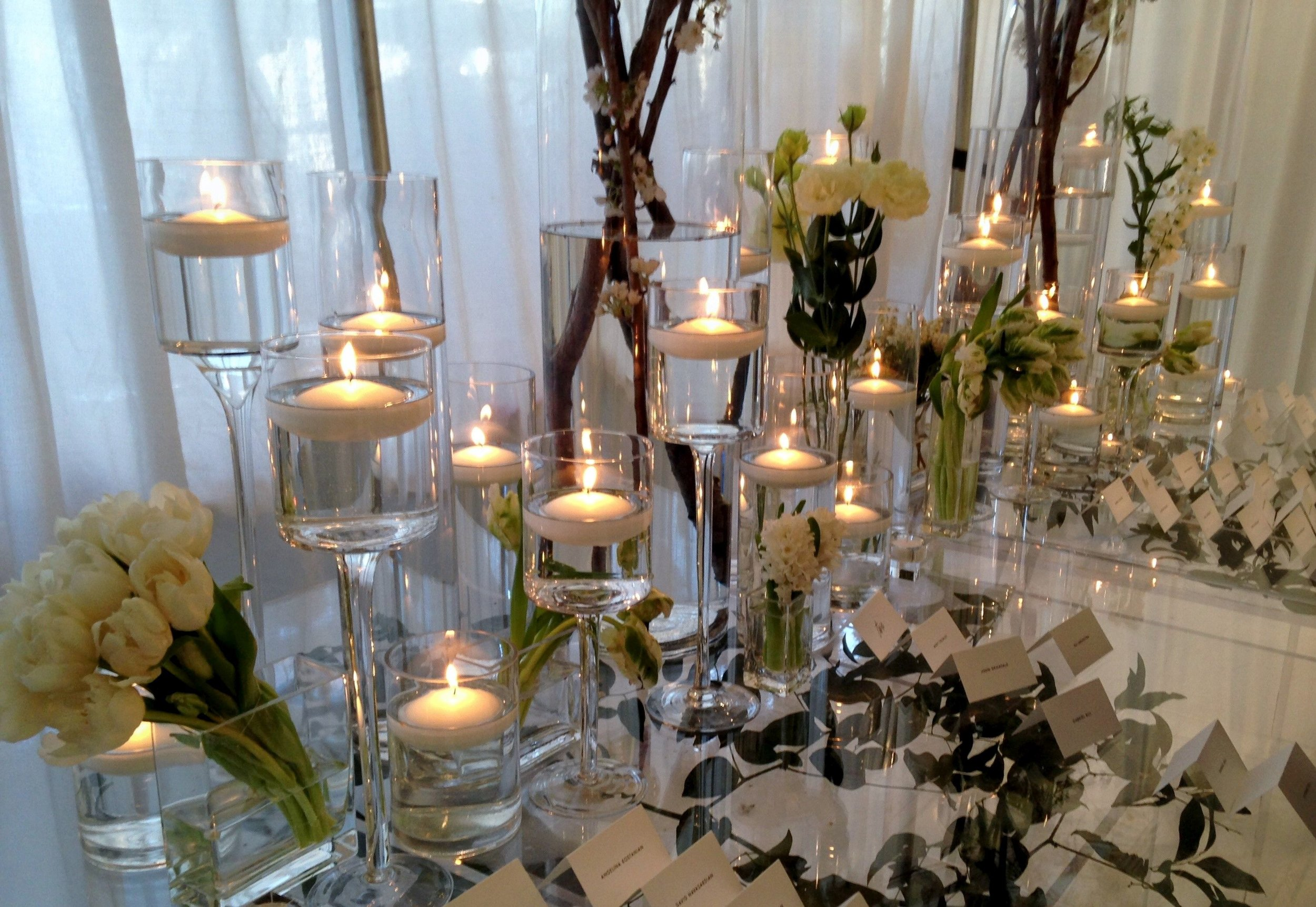 Candles and decor surrounded by simple white tulips in elegant wedding design by Bouquets & Beyond