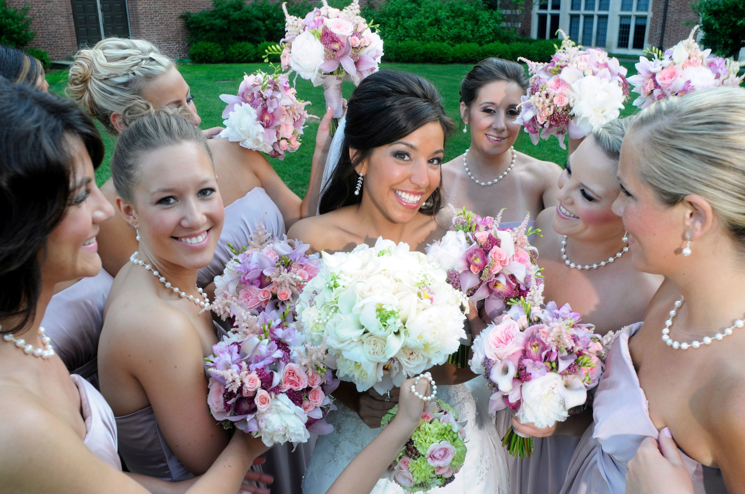 Bride holds up white bouquet of flowers while pink flowers