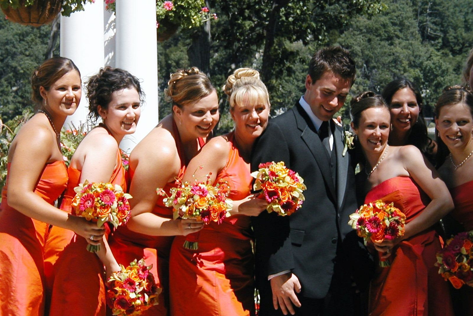 Bridesmaids in orange dresses with one of the groomsmen