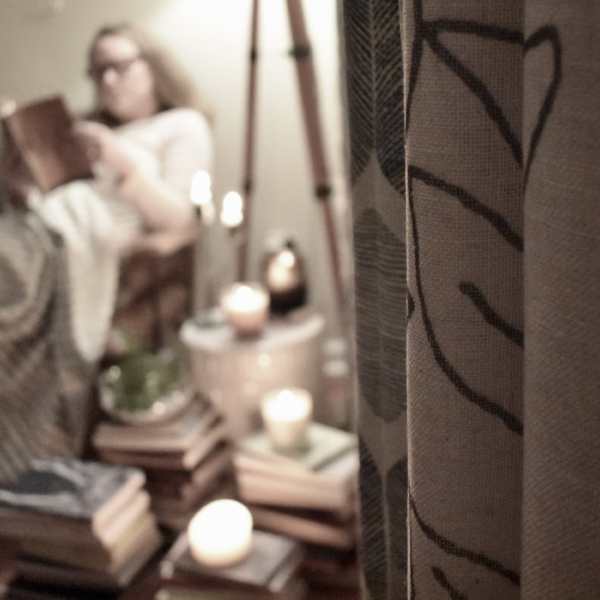 reading book in background with candles lit.jpeg