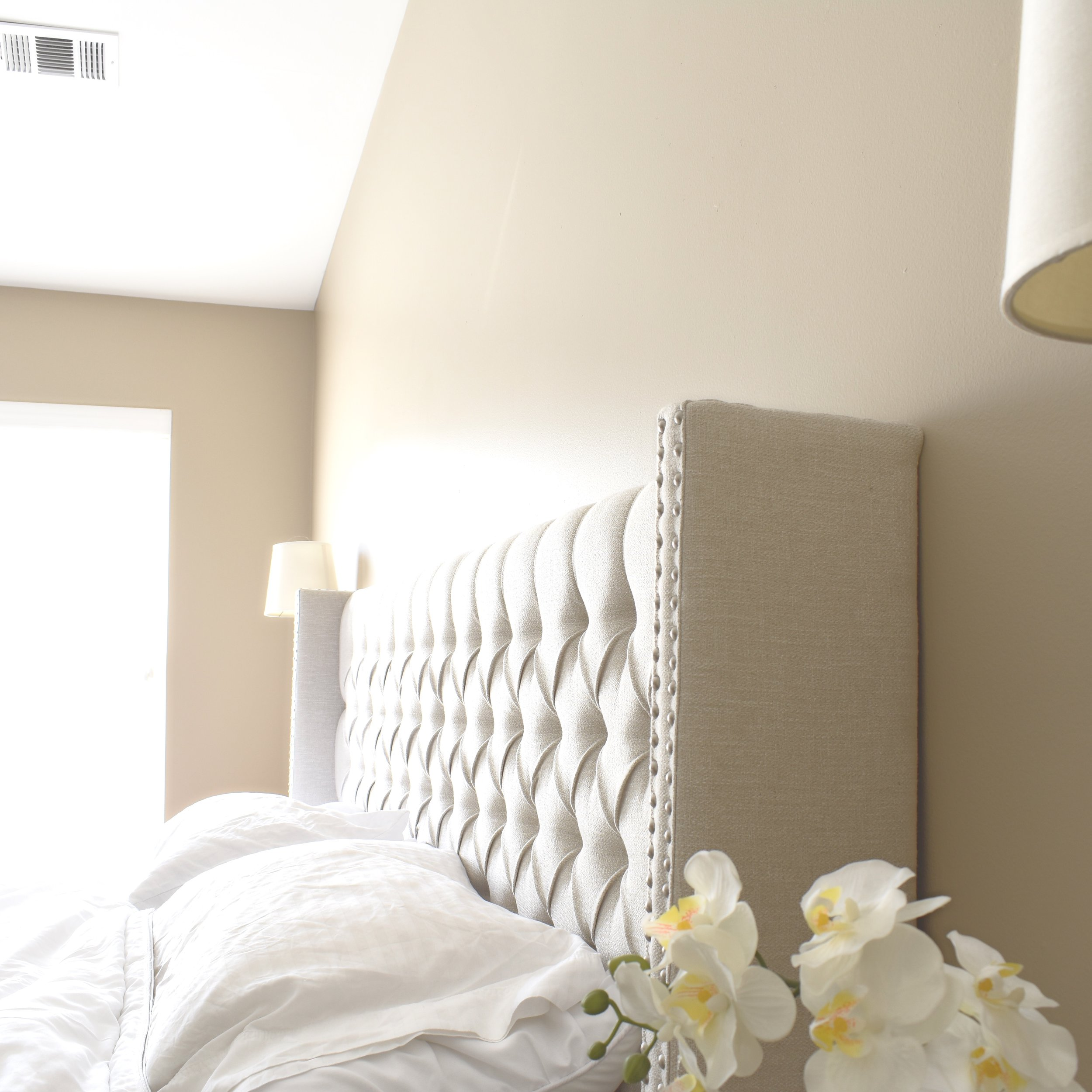 neutral master bedroom with tufted headboard and wall sconcesJPG