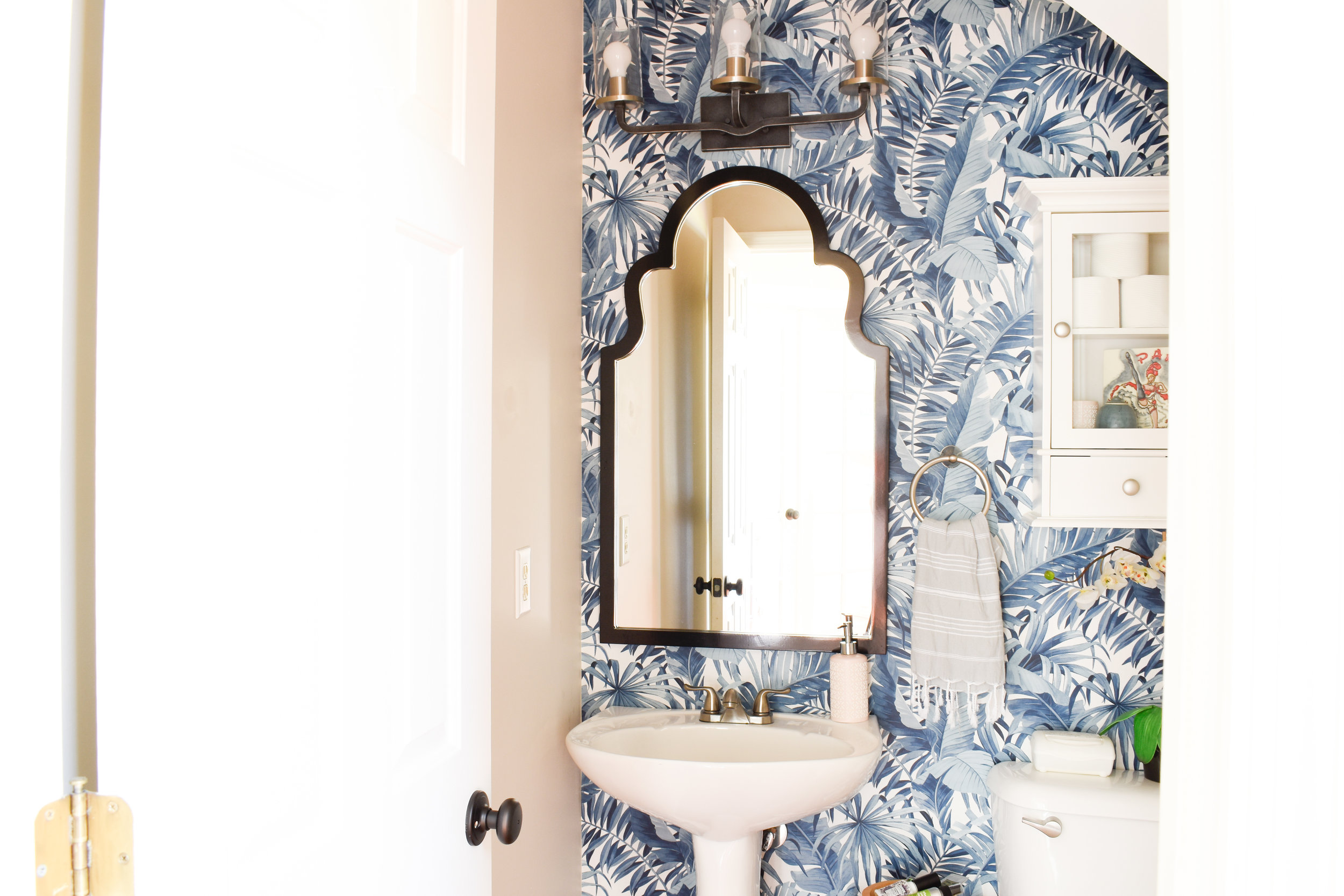 powder room with navy palm leaf wallpaper