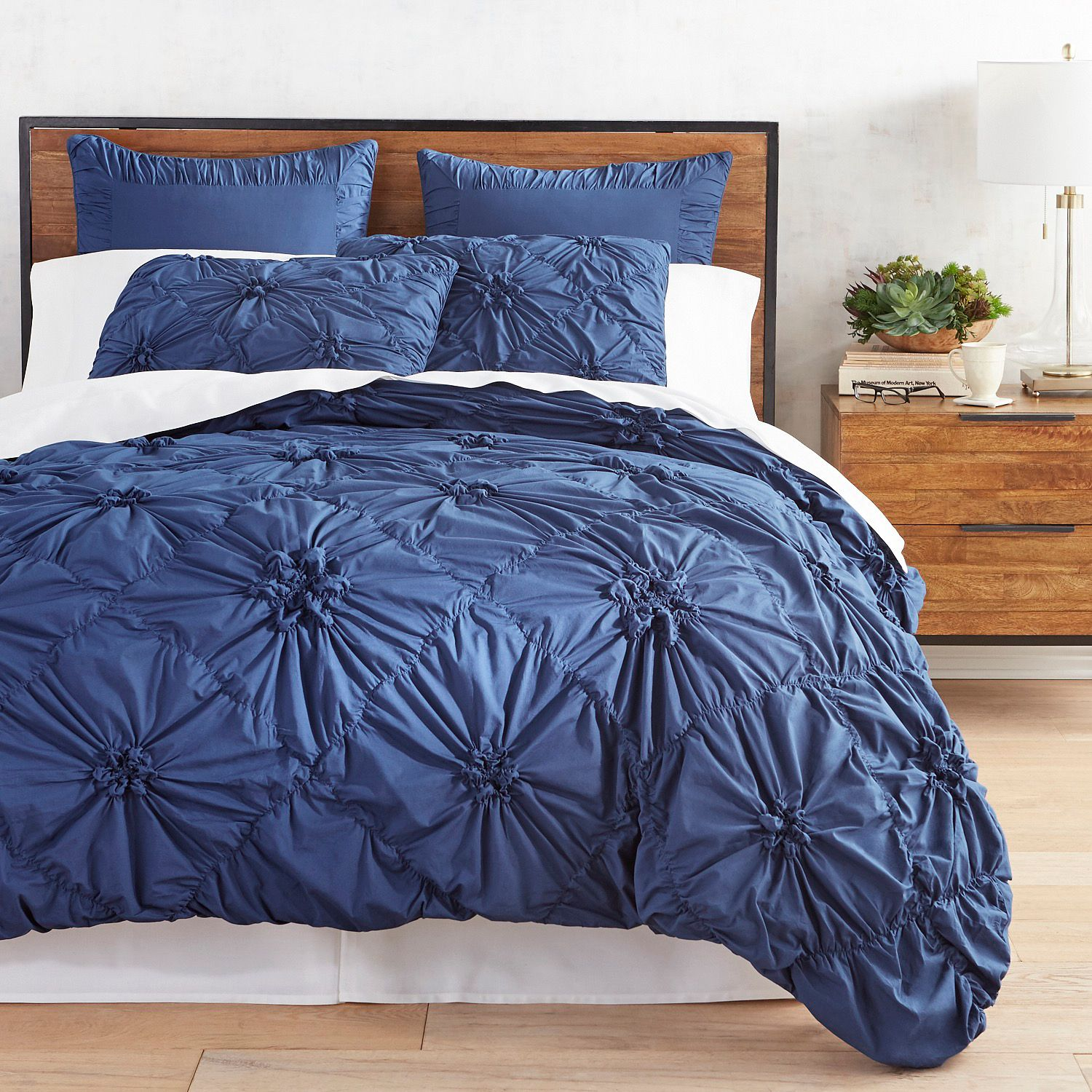 modern elegant bedroom decor in navy blue and warm wood accents