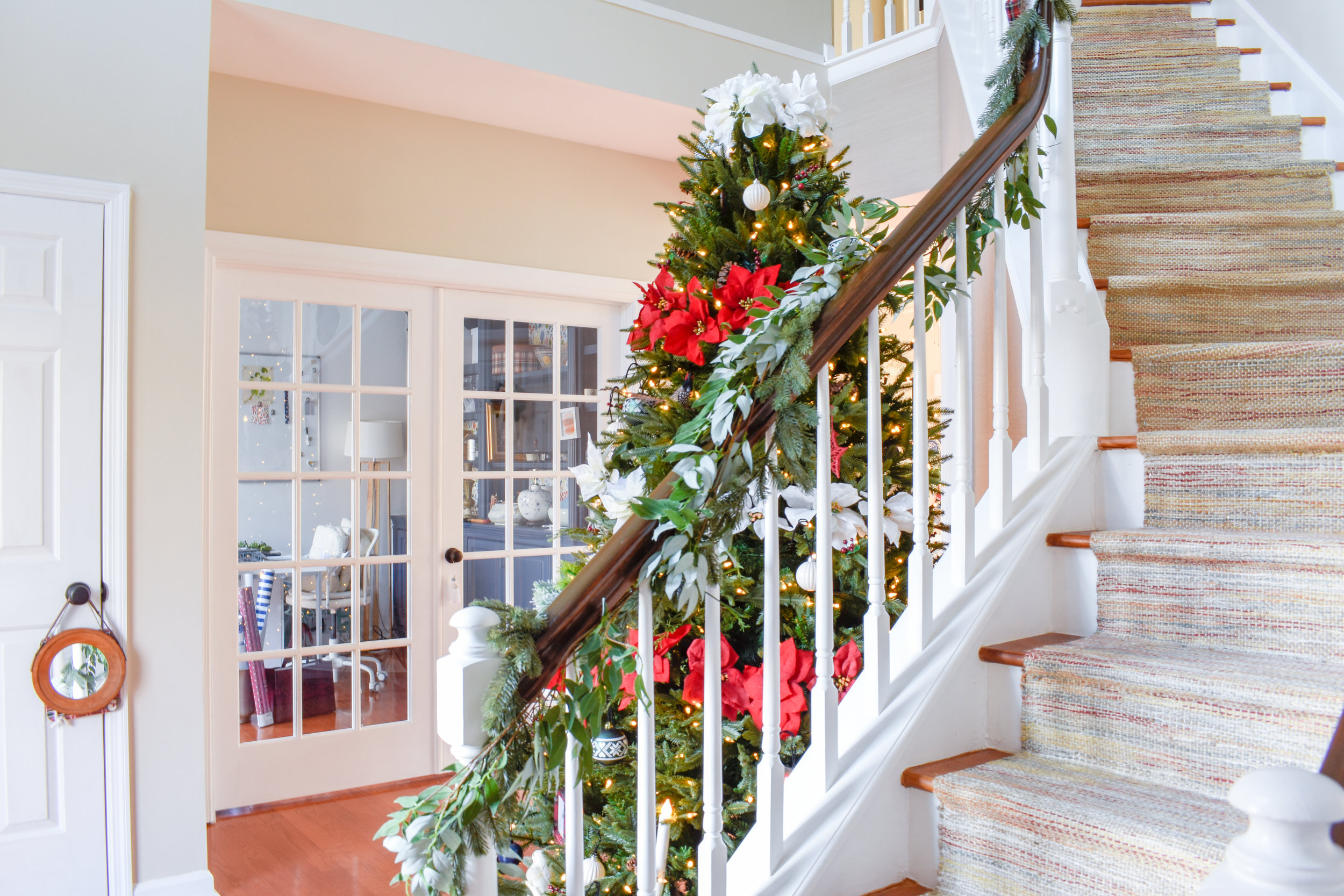 This year, we decided to put the Christmas tree in our foyer and I love it! This otherwise unused and blank space gets a fresh pop with the twirling lights and red and white color scheme. #redchristmastree #poinsettiatree