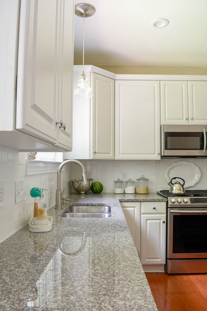 New granite countertops added such dimension to this white kitchen!