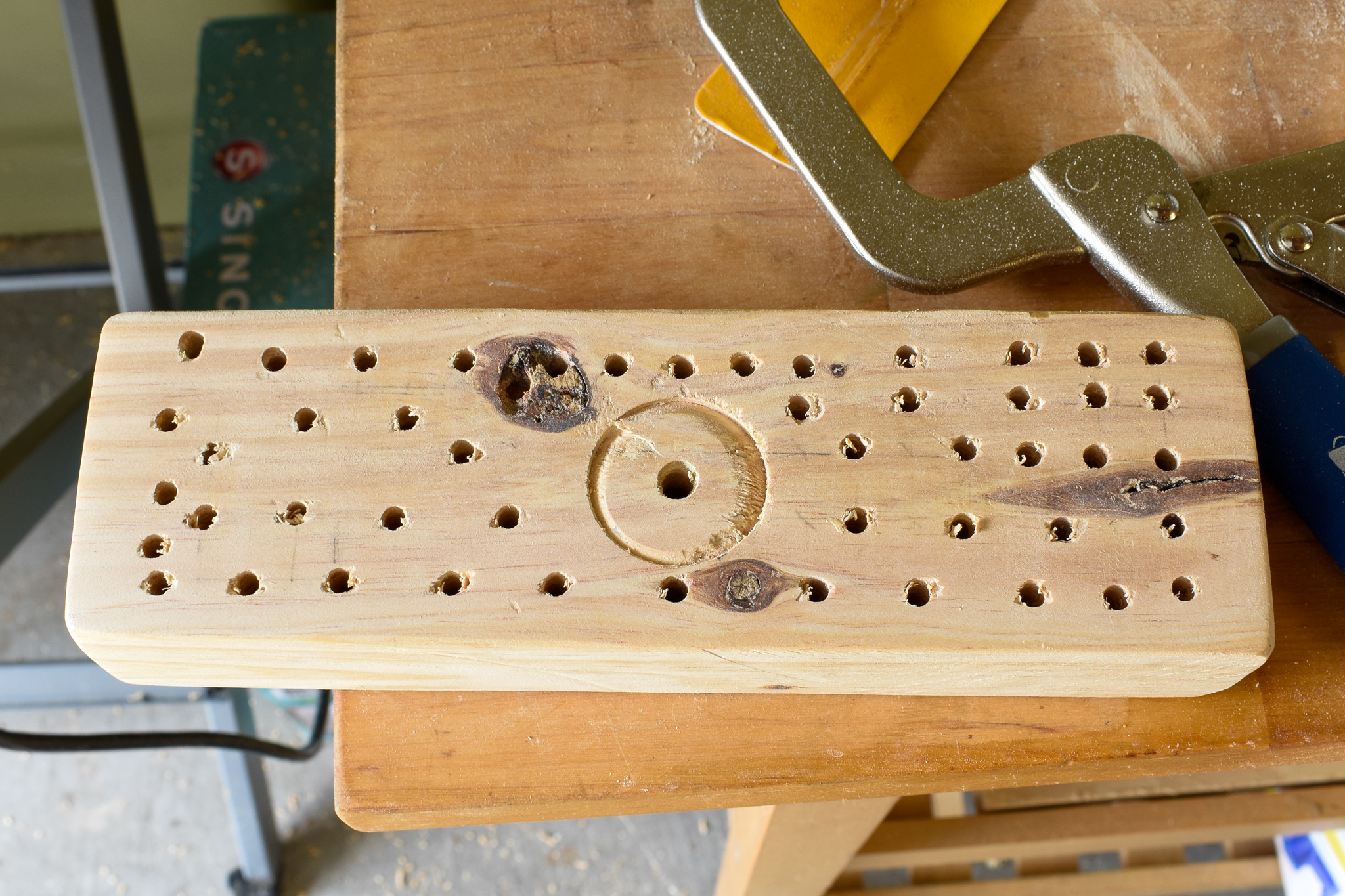 "DIY BROOM TUTORIAL: STEP SEVEN: Using the 3/8"" drill bit, create approximately 3/8"" deep holes along your grid pattern. This is where your bristles will attach to the underside of your broom. Alternate the spacing for a fuller bristle look."
