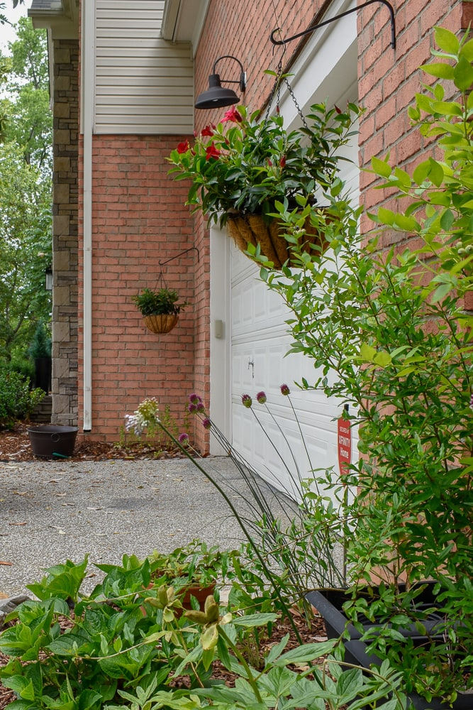 budget front yard refresh - hanging baskets add charm to a coring garage door
