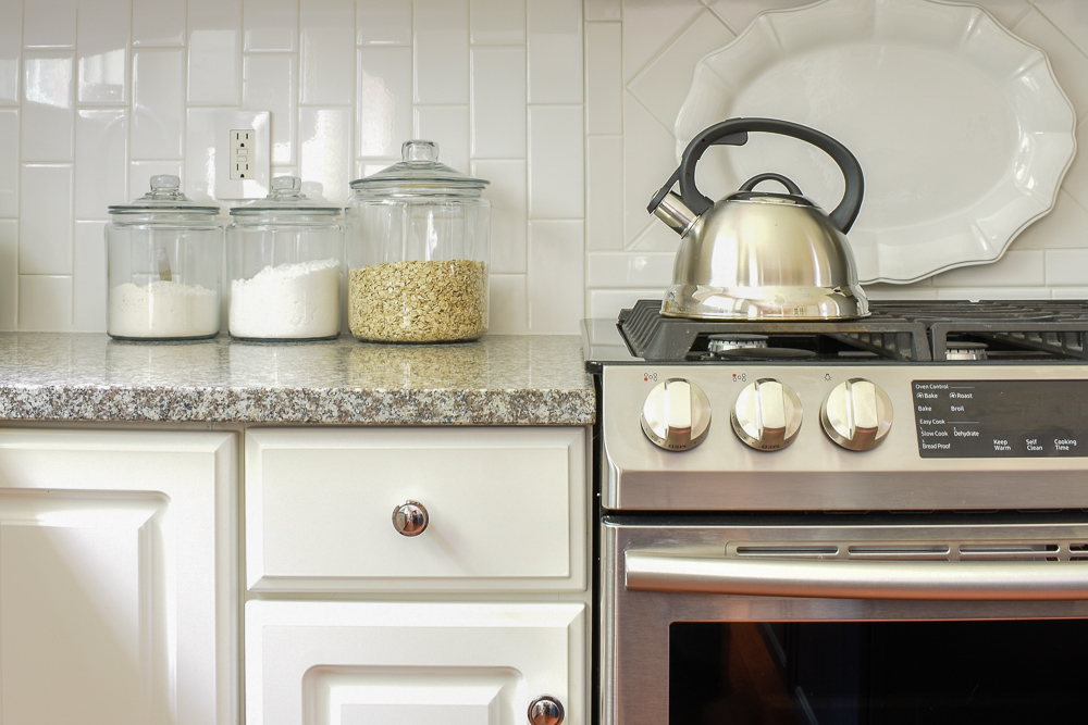 granite countertops with white subway tile backsplash and stainless steel appliances