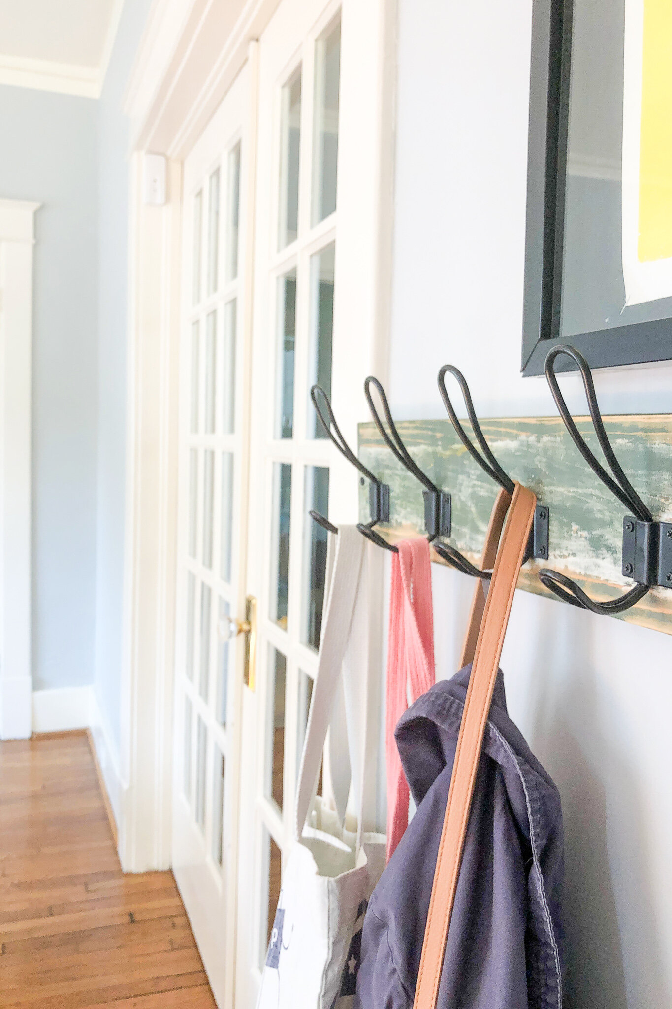 No space for storing coats? Use your walls! Here's how I added a vintage industrial style hook system in my entryway for less than $20! #schoolhousestyle #nashvillelifestyle #modernmeetsvintage #modernfarmhouse #rusticdecor