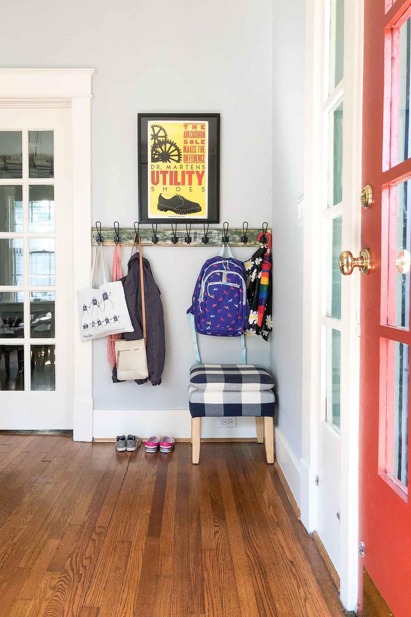 Creating a wall of storage hooks for wrangling our family's bags and outdoor gear - Here's how we made a mini-mudroom for less than $20! #schoolhousestyle #diydecor #organizationideas #backpackstorage #familystoragesolutions #colorfulhomedecor #mycuratedvibe #sodomino
