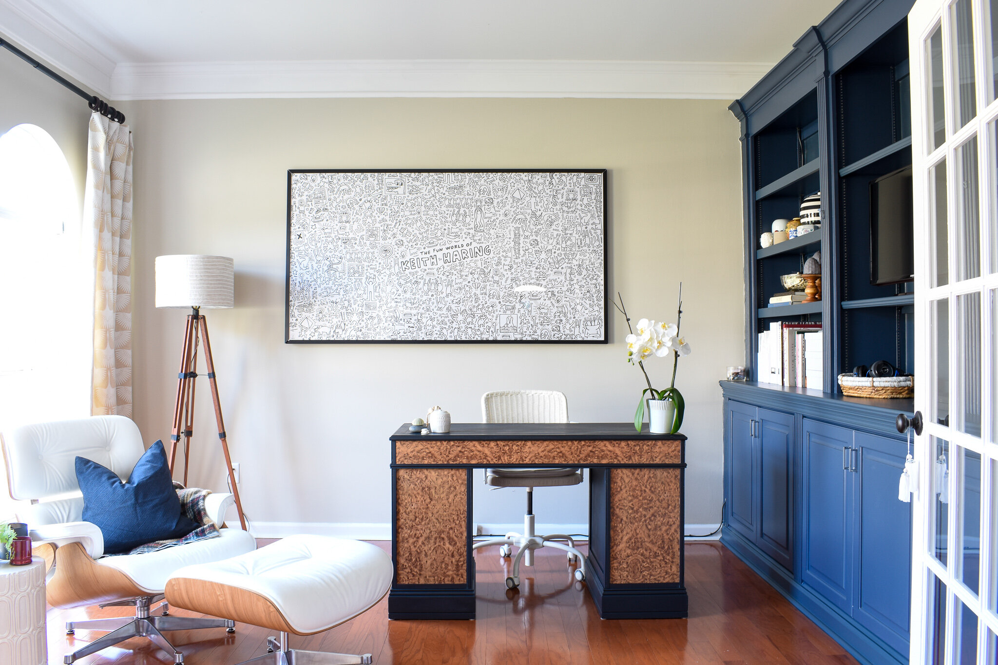 home office with built-in shelving painted navy blue