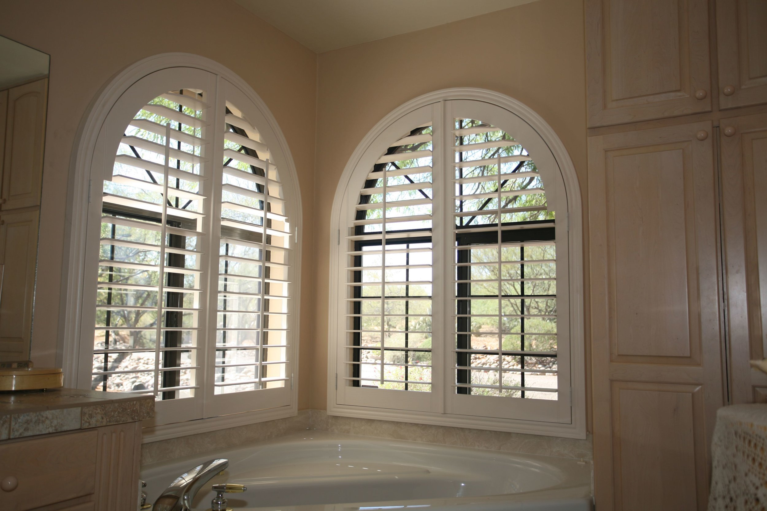 These arched window coverings are fully louvered for fine-tuned light control.