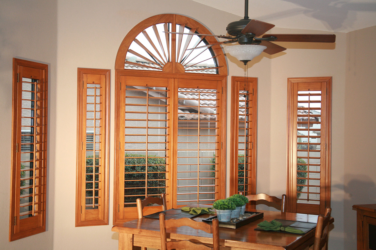 We designed a large movable sunburst arch alongside these rectangle window coverings, and stained them to match interior decor of home.