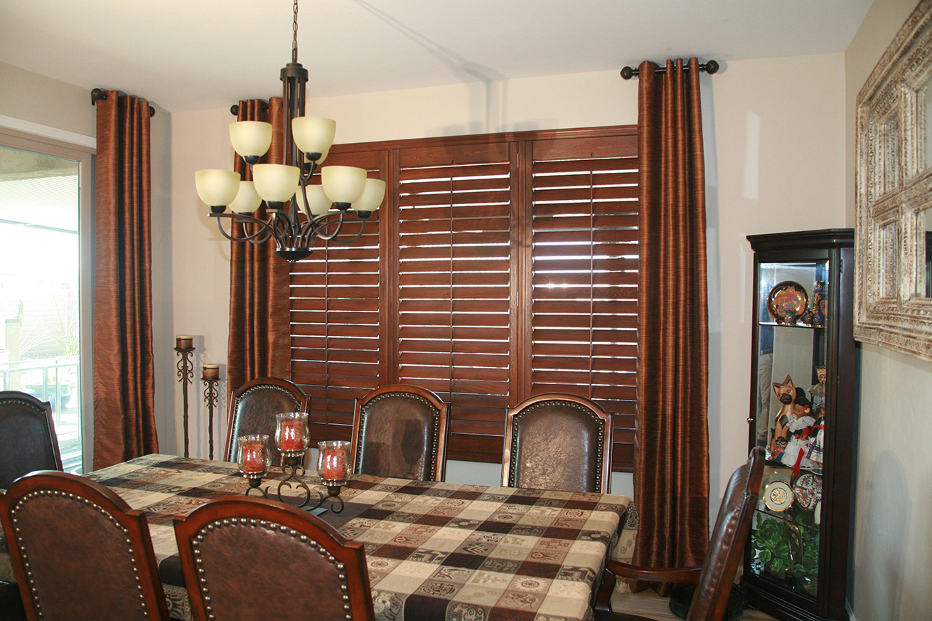 In designing these plantation shutters, we coordinated the existing drapery colors to the new louvered rectangular window coverings, matching the aesthetics of this home.