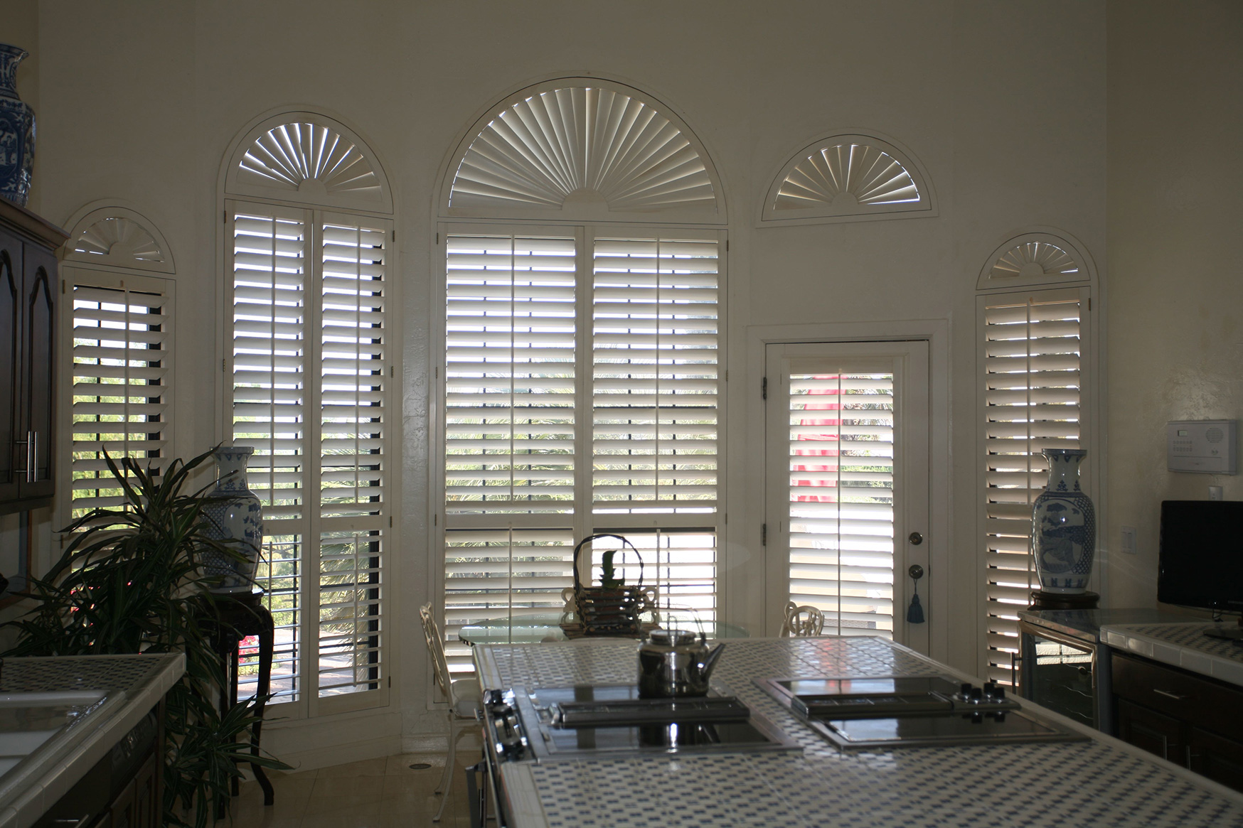 These louvered shutter panels are enhanced with movable sunburst tops.