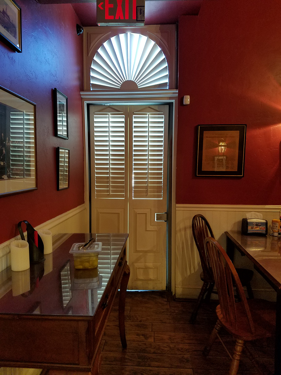 Frankie's Cheesesteak - We worked around an aesthetics issue with a very tall opening and window above it, also used as an emergency exit. We built the emergency release function of the door into the design so it maintained function & looked appealing.