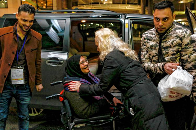 Kathryn Buckley-Brawner, center right, greets Jasimiyah Hussein and her sons Yousuf and Ayoob Al-Dulaimi, 26 and 20, all Iraqi refugees. GAZETTE STAFF/SARAH CROSBY PHOTOS)
