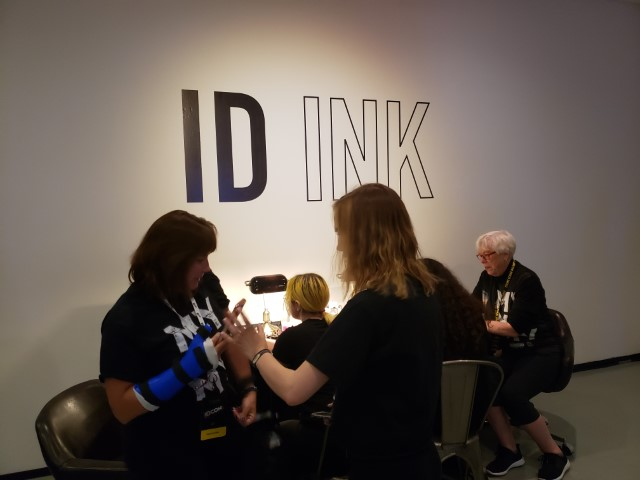 You could get your arm inked with the ID logo or another related design. (Kathy Kenda is seated to the right in the background.)