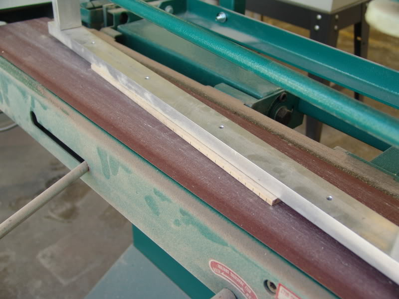 "THE SLOTTED FRETBOARD IS GIVEN ITS 9"" CROWN RADIUS ON A BELT SANDER"