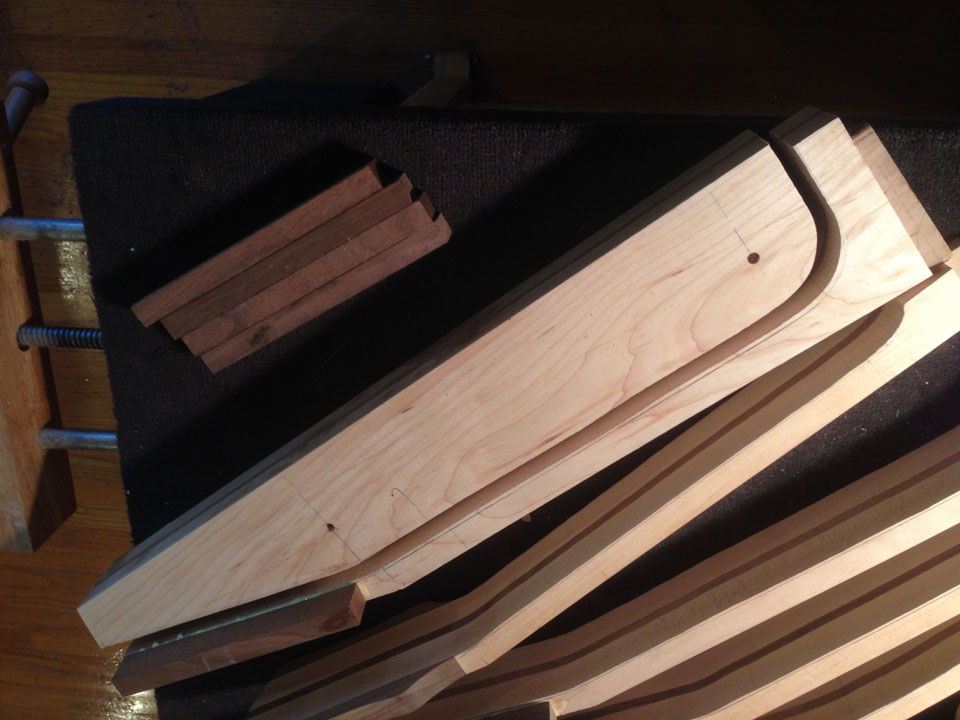 SIDE VIEW OF A LAMINATED NECK BLOCK AS IT IS CUT AWAY TO YIELD A PROFILE-TRIMMED NECK BLANK. MUCH SHAPING REMAINS TO BE DONE.