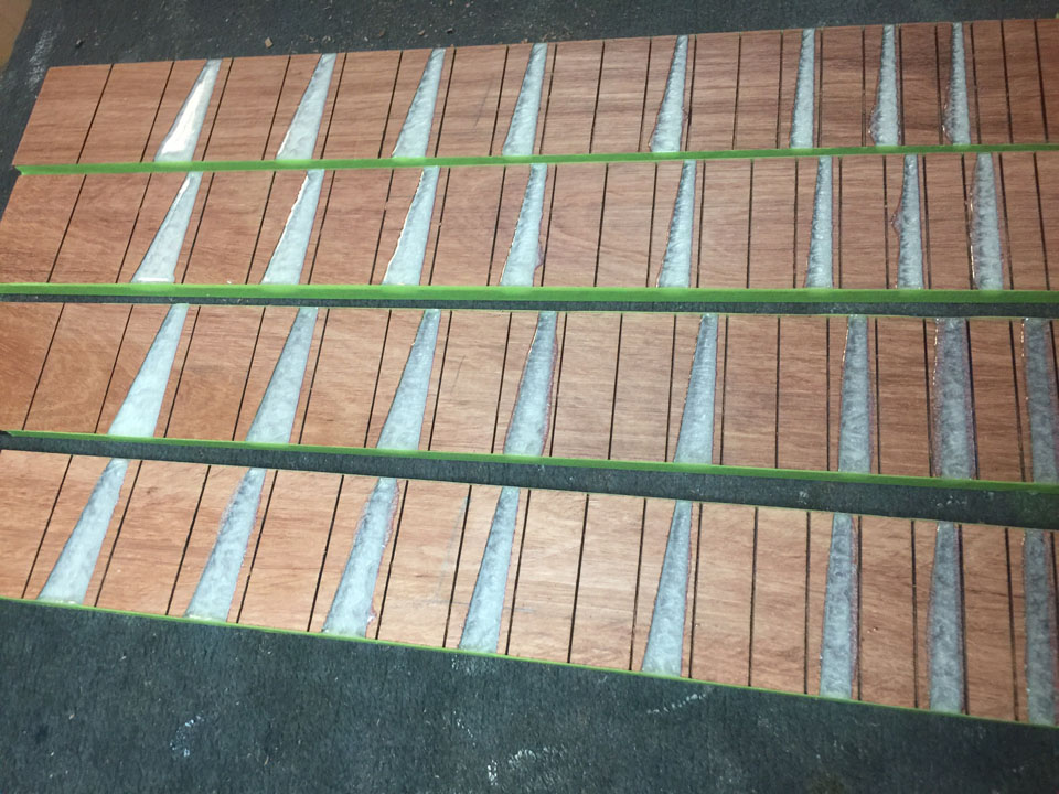 HOW THE FRETBOARDS LOOK ONCE THE FRET MARKERS ARE POURED USING PEARL LIQUID RESIN, THEN FLATTENED.