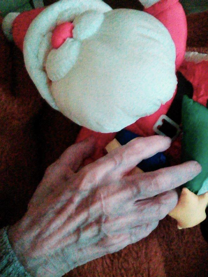 Das Bild zeigt die Hand einer Bewohnerin eines Altenheimes mit einer Weihnachtsmannpuppe.
