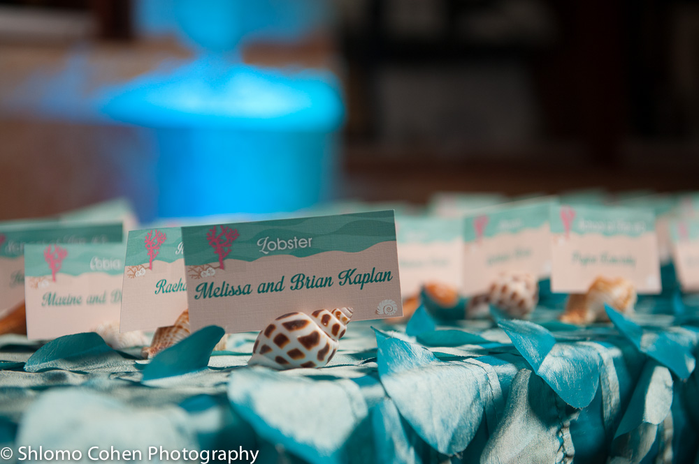 Custom designed Place Cards rested on sea shell holders