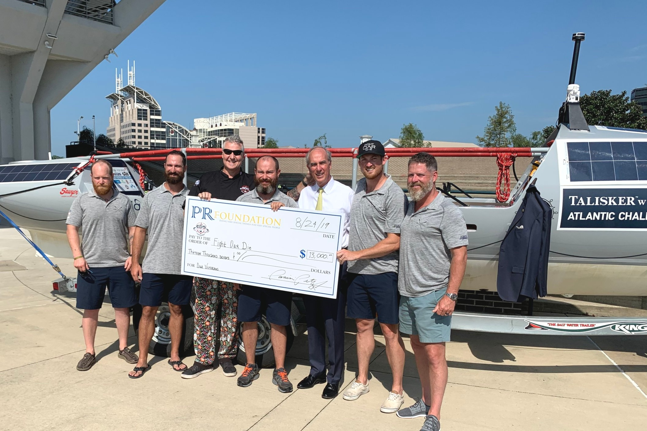 2019 PR Foundation co founder Panini Pete Blohme presenting a check for $13,000 to support the Fight Oar Die Military Veteran Team crossing the Atlantic in their boat Woobie in the Talisker Whiskey Challange .Fight Oar Die is made up of veterans from various Army backgrounds, ranging from Infantry Paratroopers, US Army Rangers and US Special Forces raising awareness of the issues veterans and their families face after they return home from combat deployment – things like Post-Traumatic Stress Disorder (PTSD), Traumatic Brain Injuries (TBI) and reintegration issues.