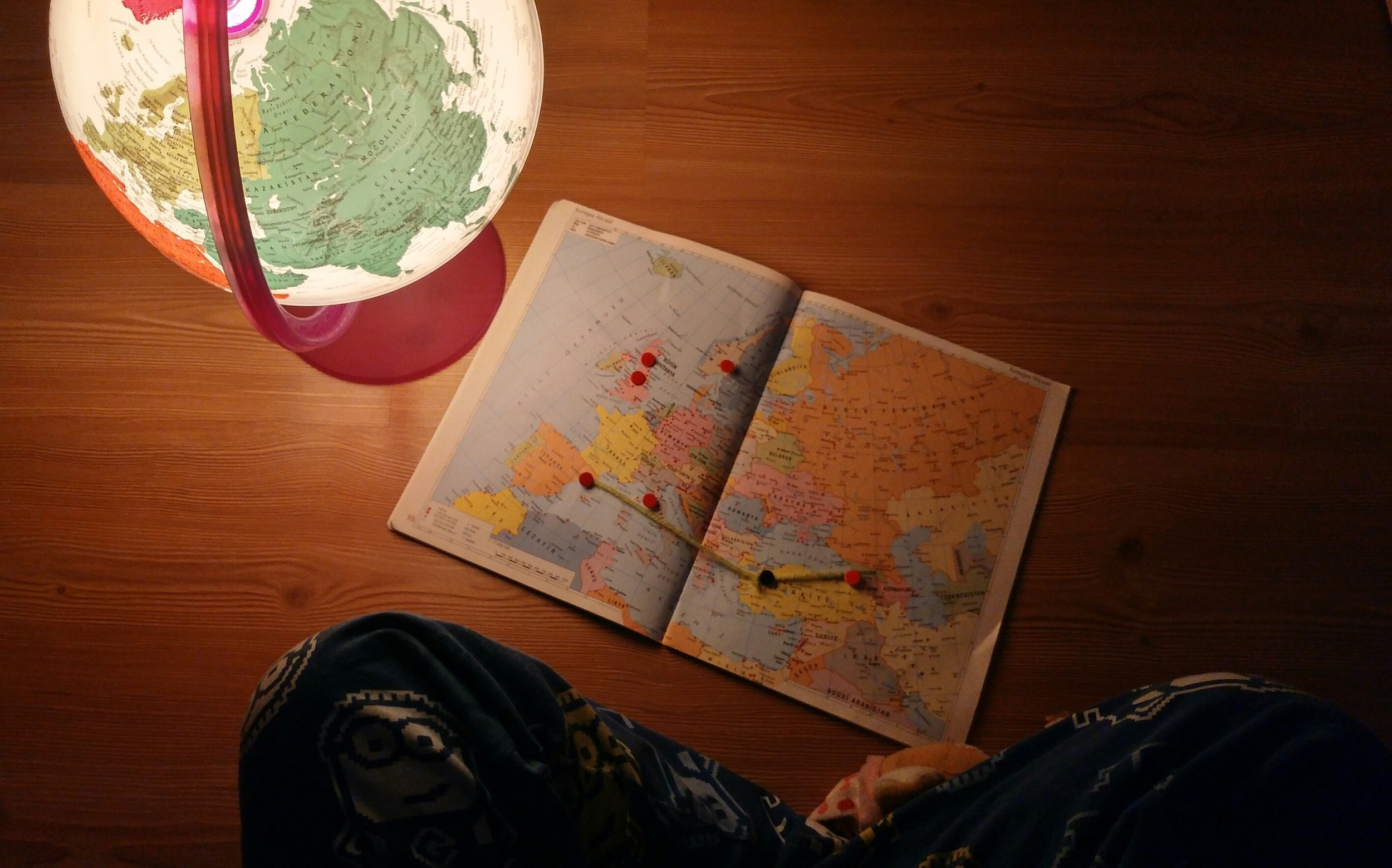 child looking at world map and globe
