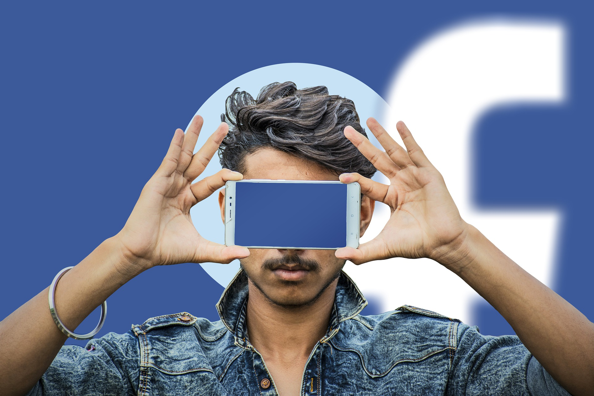 man holding smartphone over his face